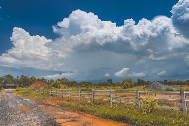 De wegomheining en de wolken van het landbouwbedrijfland in blauwe hemel scape met zonverlichting.