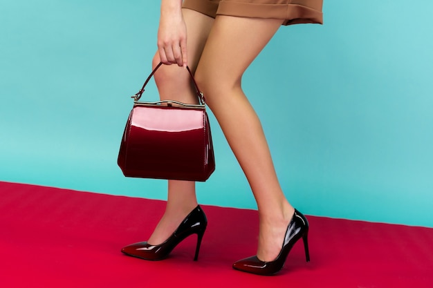 De welgevormde benen van de vrouw die zwart gelakte schoenen met hoge hakken dragen met een kleine rode handtas. close-up bekijken