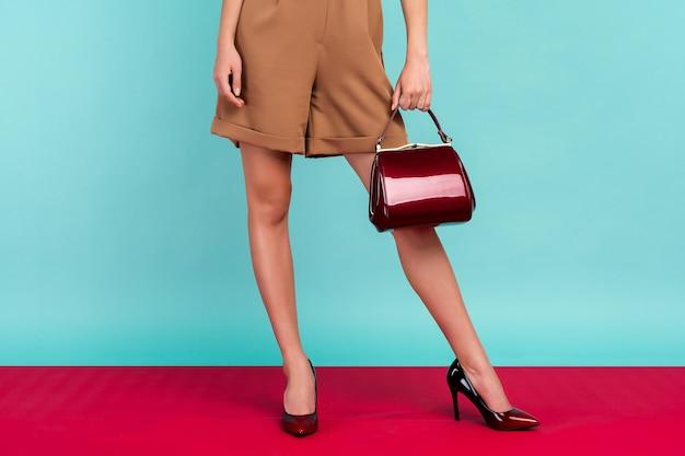 De welgevormde benen van de vrouw die zwart gelakte schoenen met hoge hakken dragen met een kleine rode handtas