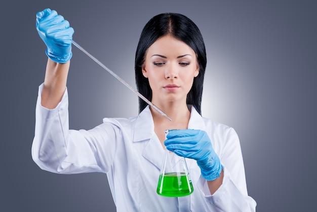 De wereld proberen te helen. mooie vrouwelijke arts in wit uniform die kolven vasthoudt terwijl ze tegen een grijze achtergrond staat