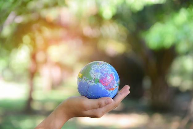 De wereldbal van de vrouwenholding op haar hand met natuurlijke groene achtergrond. wereld milieu dag concept.