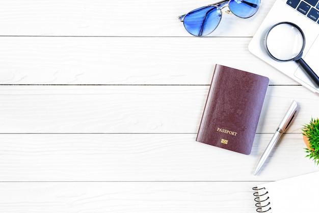 De werk- en medewerkersbalie droomt van reizen en bereidt zich voor op reis en reist de wereld over met laptop en paspoort op een witte houten tafel vanuit een vlak bovenaanzicht.