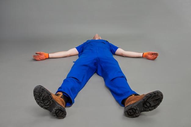 De werker ligt op zijn rug, benen naar voren. uitgeputte of dode man lag op de vloer. de installateur zwijmelt op de vloer