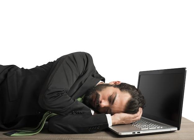 De werklast van de zakenman valt moe op de computer in slaap