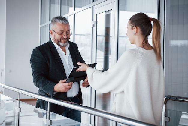 De werknemer gaat de documenten in klassieke kleding van de zakenman afnemen