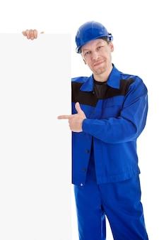 De werknemer in blauwe uniform wijzend op leeg bord billboard