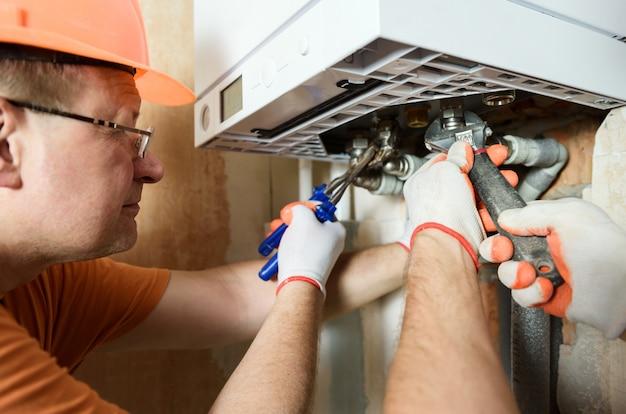 De werknemer installeert de leidingen van de gasketel.