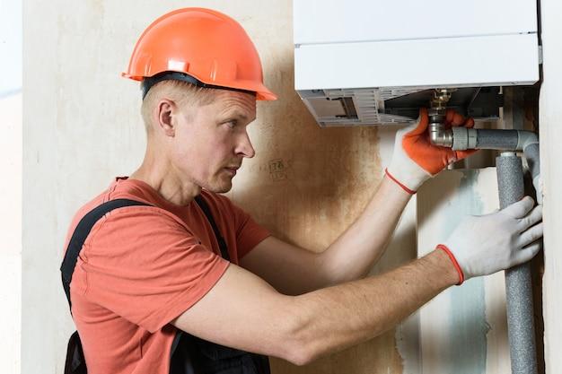 De werknemer installeert de leidingen van de gasketel