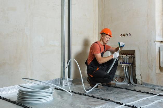 De werknemer installeert een pijp voor de warme vloer in het appartement.