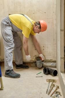 De werknemer installeert een rioolafvoerleiding om de ingebouwde tank van het toilet te installeren