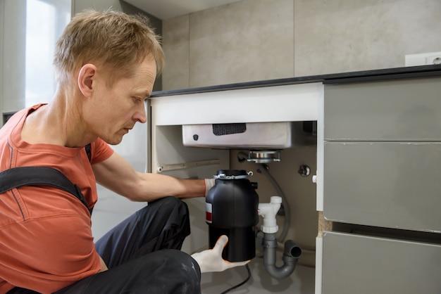 De werknemer installeert een shredder voor huishoudelijk afval voor de gootsteen.