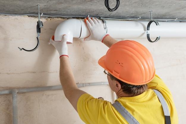 De werknemer installeert een ventilatiesysteem in het appartement