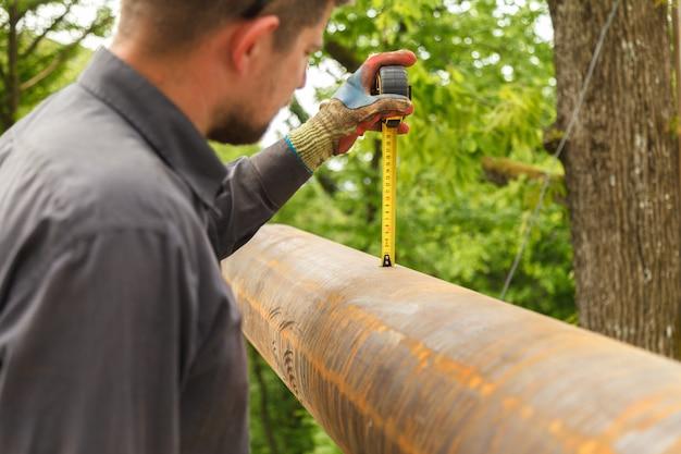 De werknemer meet de hoogte van de metalen buis met het laserniveau.