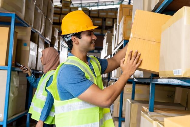 De werknemer met een doos in het magazijn