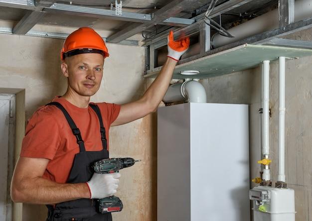 De werknemer monteert een complex frame voor gipsplaat aan het plafond