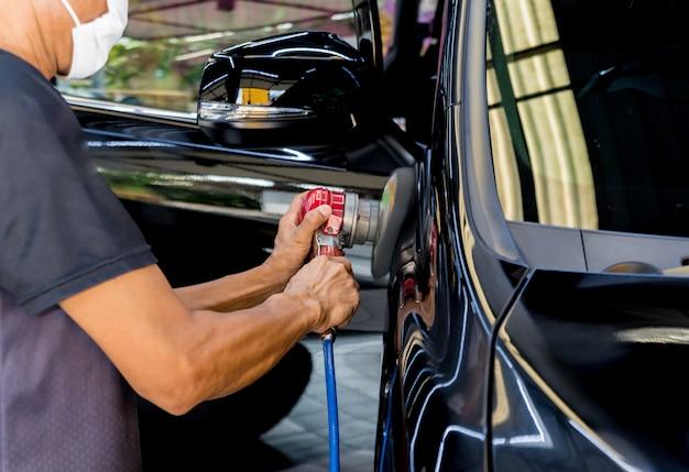 De werknemer poetst een auto met het elektrische gereedschap.