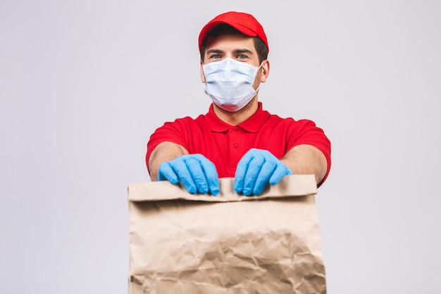 De werknemer van de leveringsman in de rode glb-lege handschoenen van het t-shirt eenvormige gezichtsmasker houdt lege kartondoos die op witte muur wordt geïsoleerd. service quarantaine pandemisch coronavirus virus 2019-ncov concept.