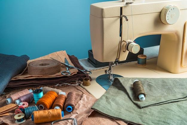 De werkplaats van de naaister op een blauwe achtergrond. zijaanzicht met kopie ruimte.