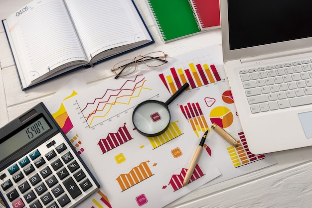 De werkplek van bedrijfsanalisten met grafieken, rekenmachine en laptop