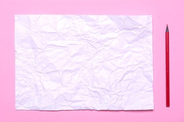 De werkplek van de kunstenaar. een vel verfrommeld papier op een roze achtergrond. textuur van wit papier, potlood en canvas voor tekenen.