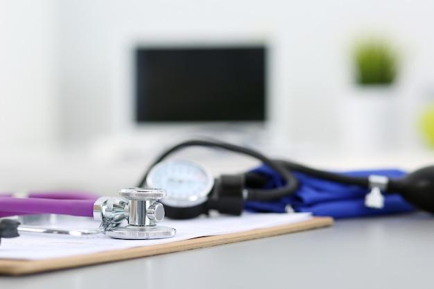 De werkplek van een medicijndokter. stethoscoop en manometer liggend op tafel op het kantoor van arts. gezondheidszorg, gezondheid en medisch concept