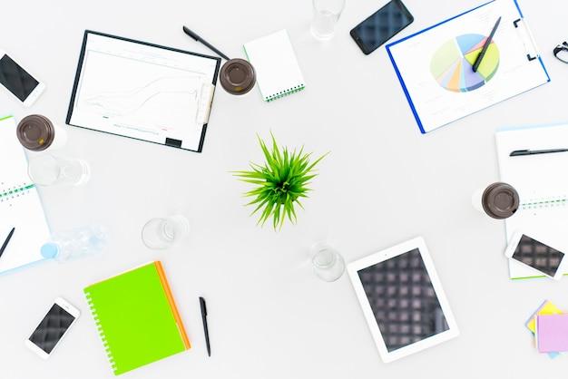 De werkruimte met een tablet, telefoons en papieren