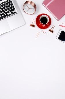 De werkruimte van het huisbureau met smartphonotitieboekje en laptop op witte achtergrond.