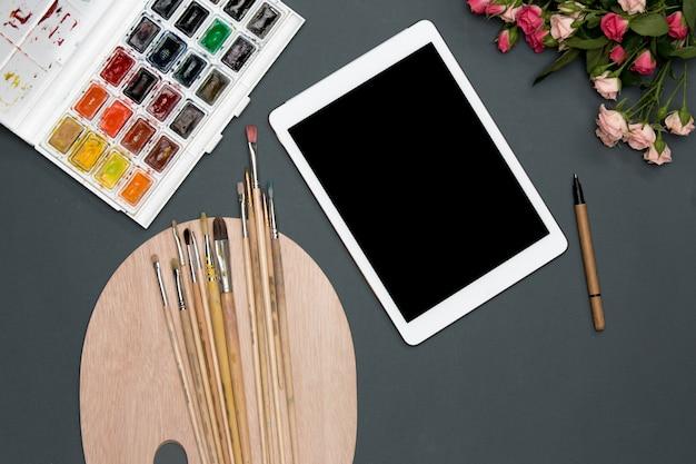De werkruimte van kunstenaar met laptop, verf, penselen, bloemen op zwart