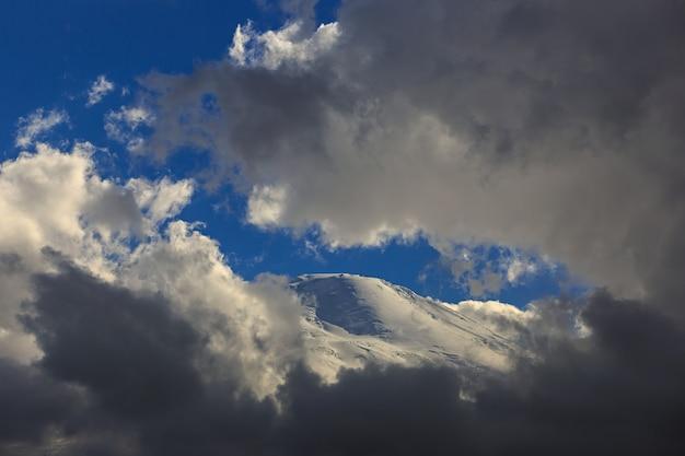 De westelijke piek van onderstel elbrus, de helling met sneeuw is zichtbaar door de wolken. bergketen in de noord-kaukasus in rusland.
