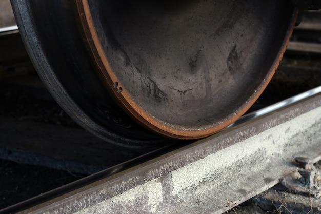 De wielen van een oude roestige kapotte goederentrein staan op de rails