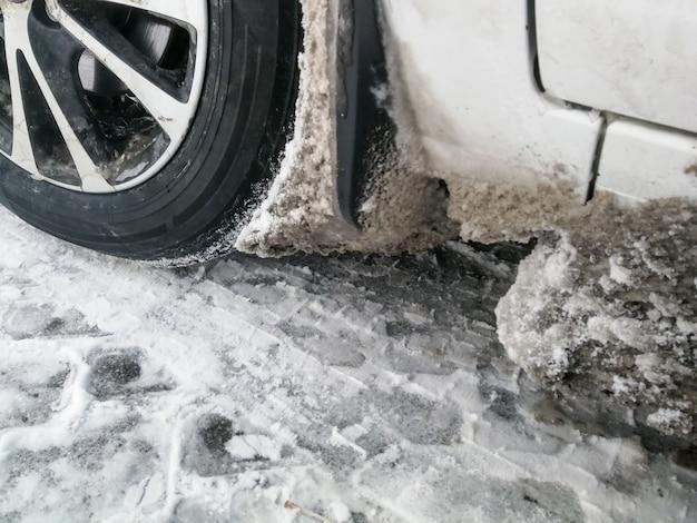 De wielkast van de auto is verstopt met ijs en sneeuw