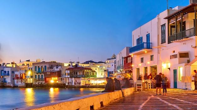 De wijk little venice met bars en restaurants aan zee op het eiland mykonos in de schemering, griekenland. grieks resort 's nachts