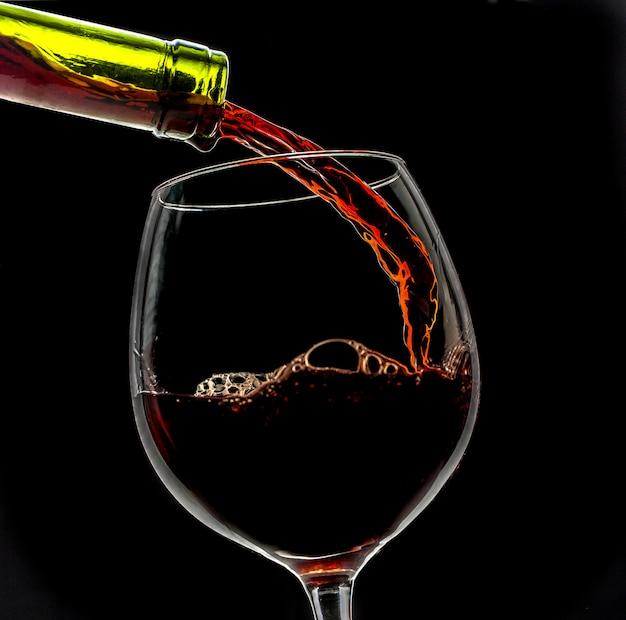 De wijn van de druif die in wijnglas wordt gegoten op zwarte achtergrond