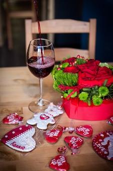 De wijn wordt in een glas gegoten. rood boeket, voor valentijnsdag