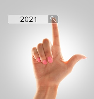 De wijsvinger van een hand wijst naar het zoekveld met nieuwjaarsconcept