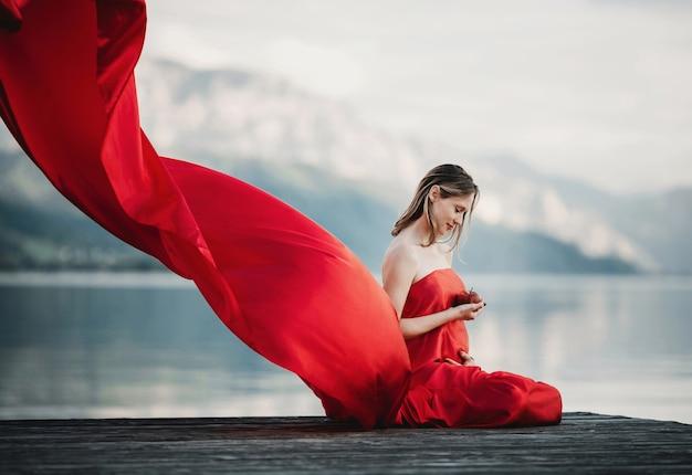 De wind blaast rode kleding van een zwangere vrouw die met appel op de brug over het meer zit