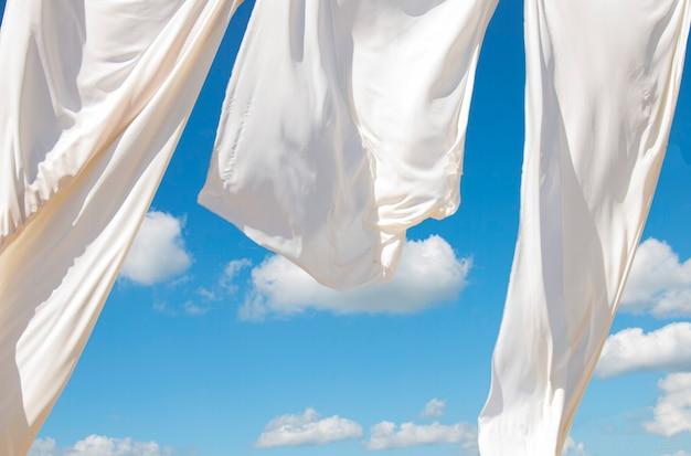 De wind blaast witte luifels aan de kust tegen de blauwe lucht