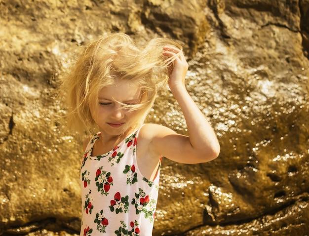 De wind speelt het haar in blond meisje