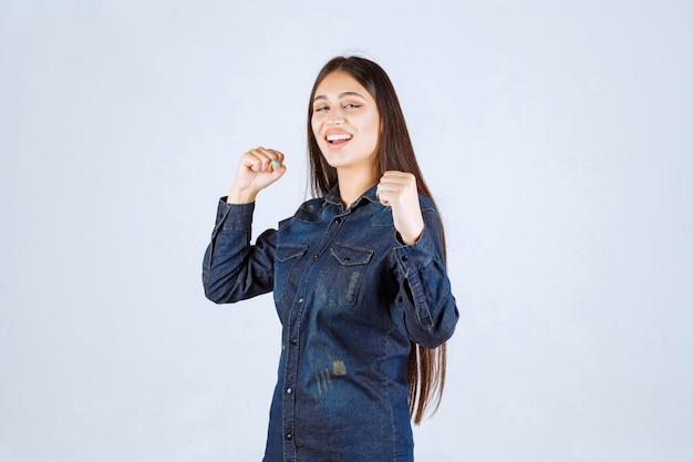 De winnaar jonge vrouw toont haar vuisten en voelt zich krachtig