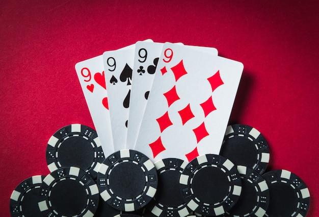 De winnende pokercombinatie is four of a kind of quads. chips en kaarten op de rode tafel in de pokerclub