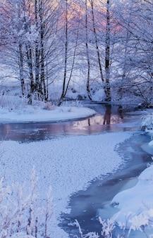 De winter rivier bij zonsondergang