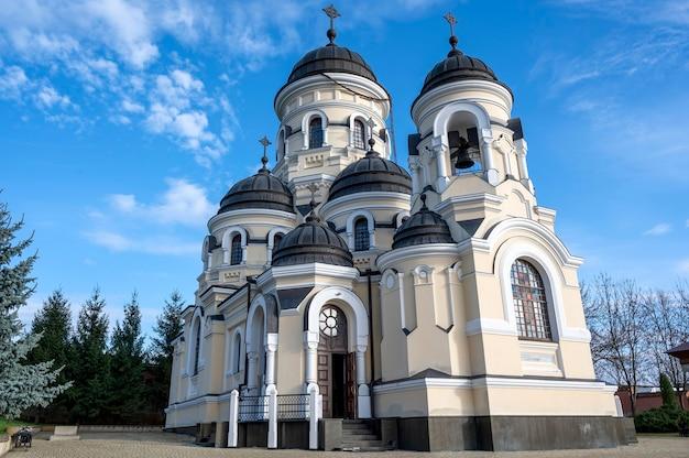 De winterkerk en de binnenplaats van het capriana-klooster. kale bomen, mooi weer in moldavië