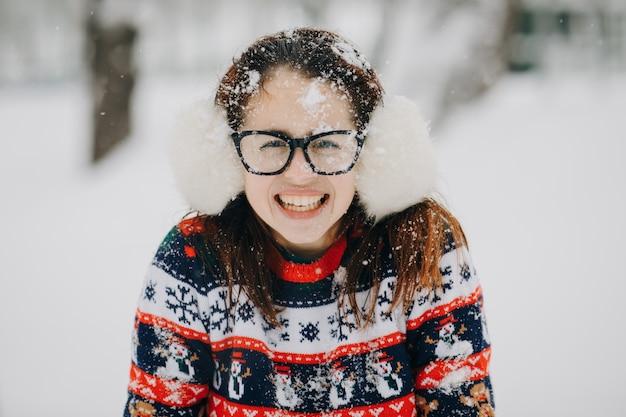 De winterportret van jong mooi meisje die oormoffen, sweater het stellen in sneeuwpark dragen. vrouw op zoek