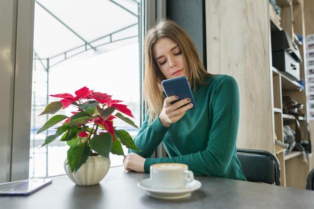 De winterportret van jonge mooie meisjeszitting bij koffie