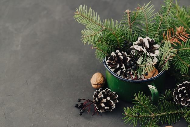 De wintersamenstelling van nette takken, pinecone, noten in uitstekende mok op donkere achtergrond