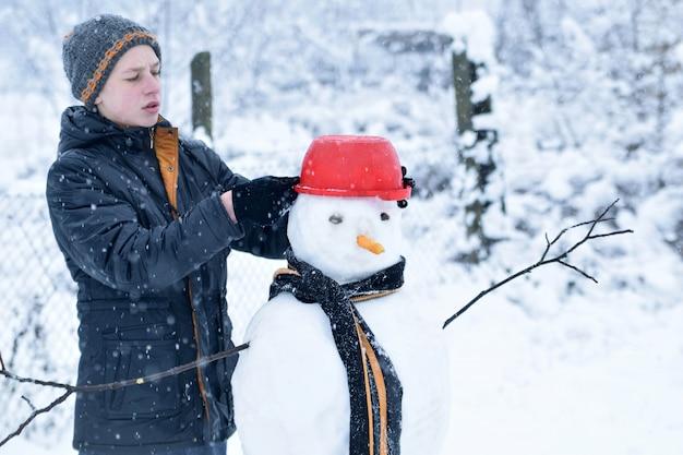 De wintertiener in een jasje en een hoed beeldhouwt een sneeuwman op een de winterachtergrond met dalende sneeuw in bevroren dagconcept