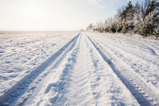 De winterweg op een landelijk gebied