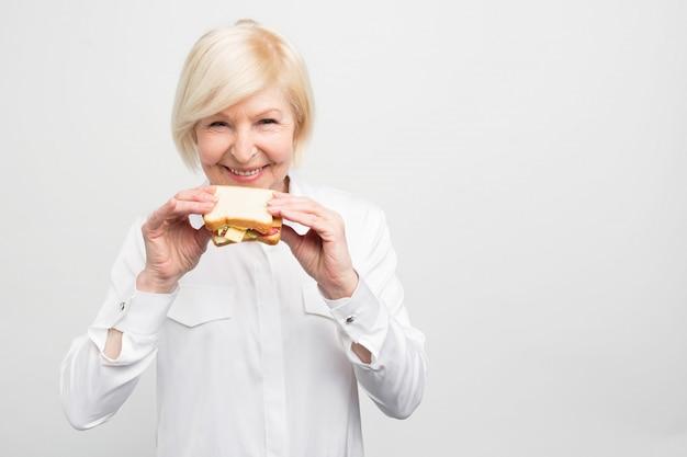 De witharige vrouw staat en houdt een lekker en goed stuk boterham vast. ze heeft geen tijd om een betere maaltijd te eten. se geniet ervan het te eten.