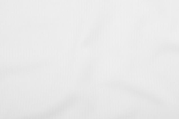 De witte achtergrond van de stoffentextuur met zachte golven.