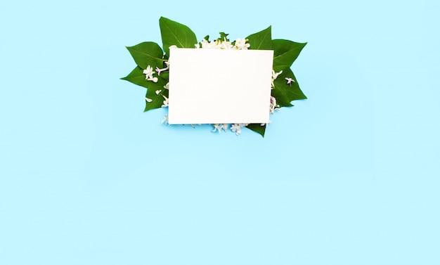 De witte ansichtkaart rust op groene bladeren en witte lila bloemen met een blauwe achtergrond. een plek voor tekst.